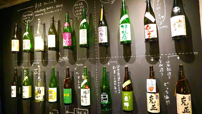 牆壁上放著一公升的日本酒瓶和手寫說明文