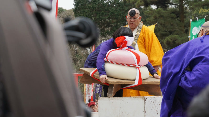 people are trying to lift up the huge rice cake