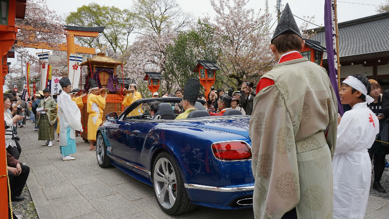 The chief priest is riding the blue car behind the portable shrine