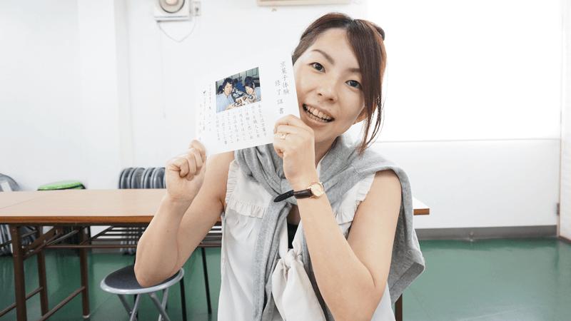 Yoko smiles with her diploma