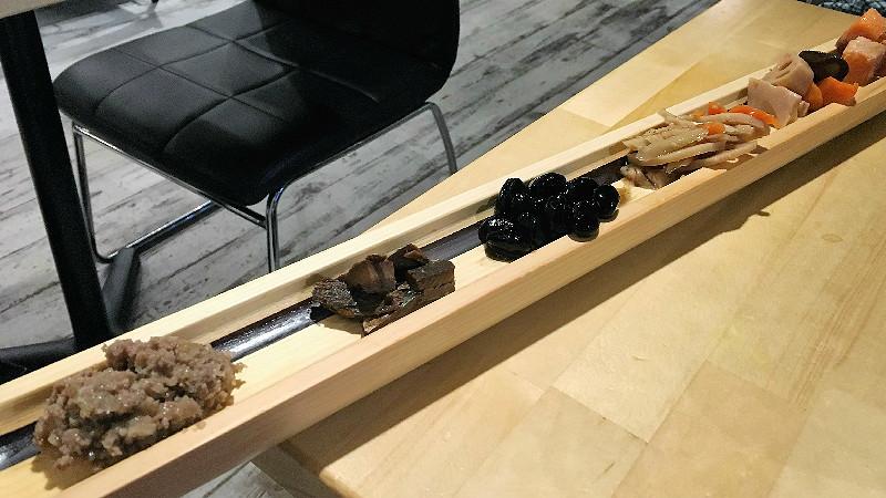 這細長竹板上放上8種下酒菜