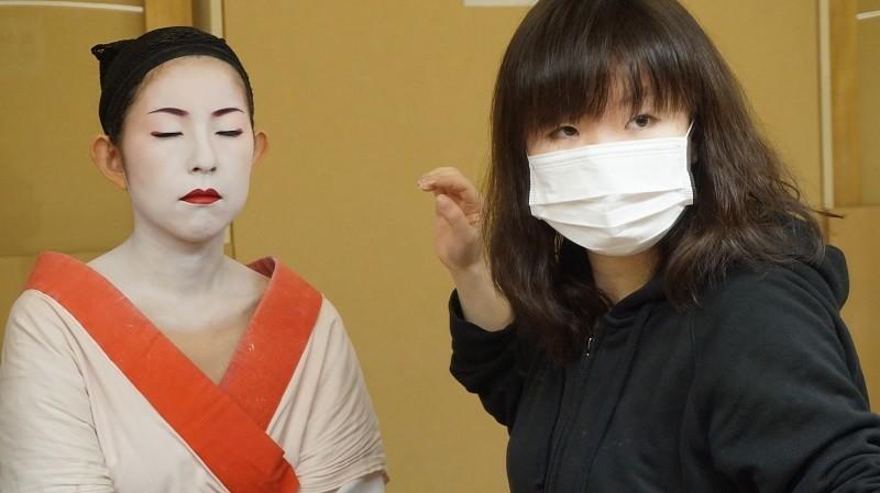化妝師在鏡中檢查她的工作成果